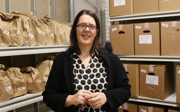 Helen Robinson in front of shelves of food parcels in paper bags and cardboard boxes