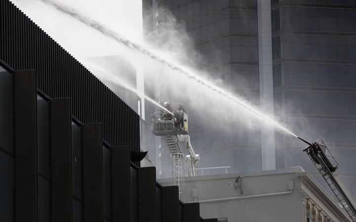 a lifter with fire fighters using a hose to fight spray over a wall and another with an mecanical hose