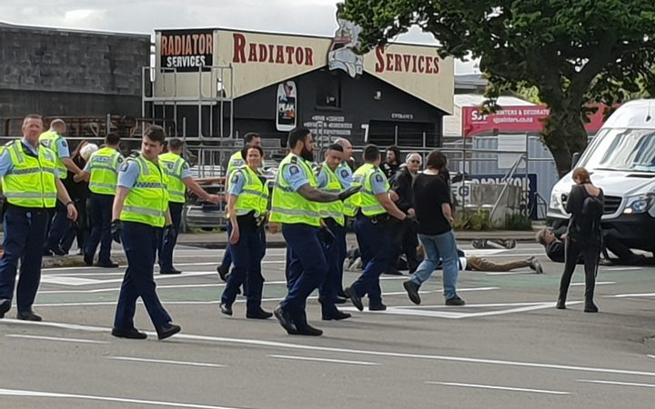 several protestors on a road, mostly obscured by a forming line of police in yellow vests