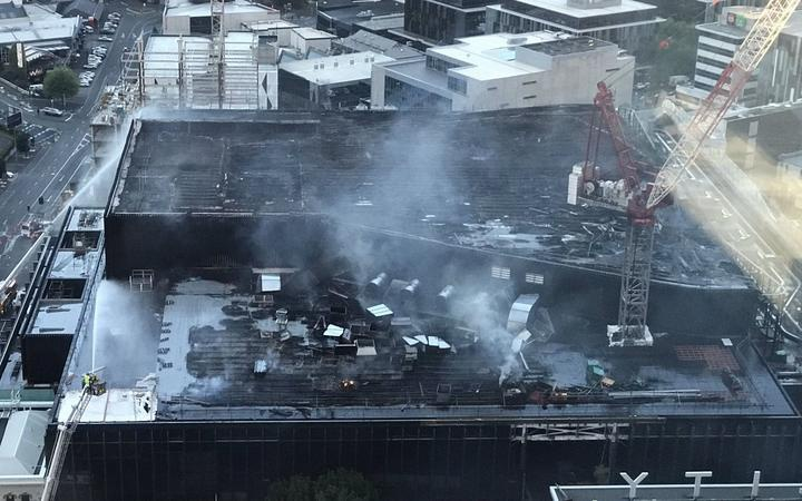 a large split-level flat rooftop with charred rafters showing over most of the area, smoke and jets of firehose water