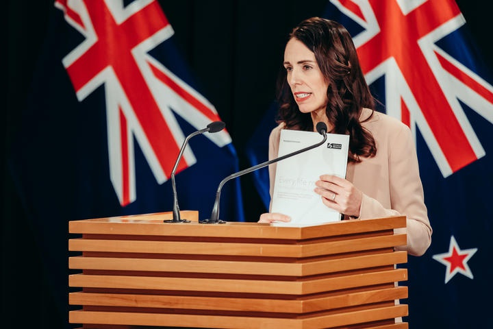 Ardern at the beehive theatrette lectern holding up the document