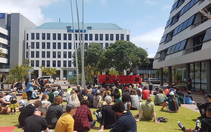 people sitting on grass in the square, listening to speakers