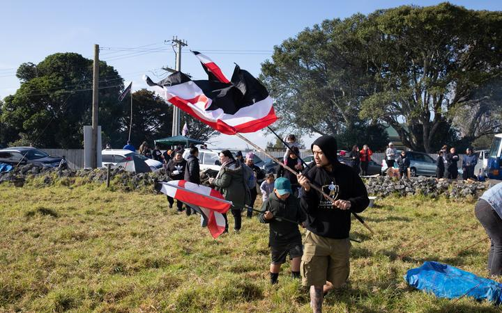 people waving tino rangitriatanga flags, and other people