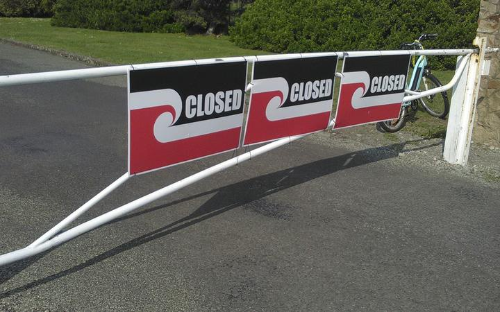 a closed steel bar road gate, with signs showing the tino rangatiratanga flag and the word CLOSED
