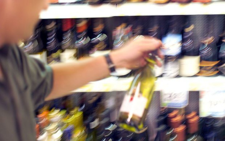 a person picking upa wine bottle off a store shelf
