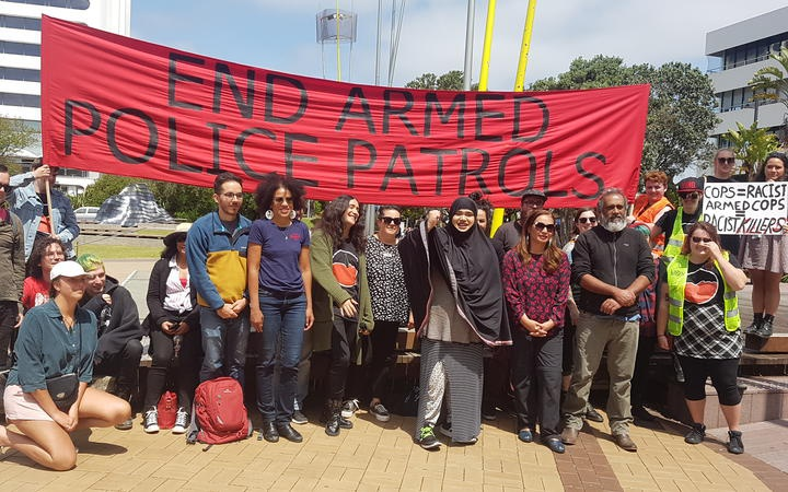 a group of people under a banner reading: END ARMED POLICE PATROLS