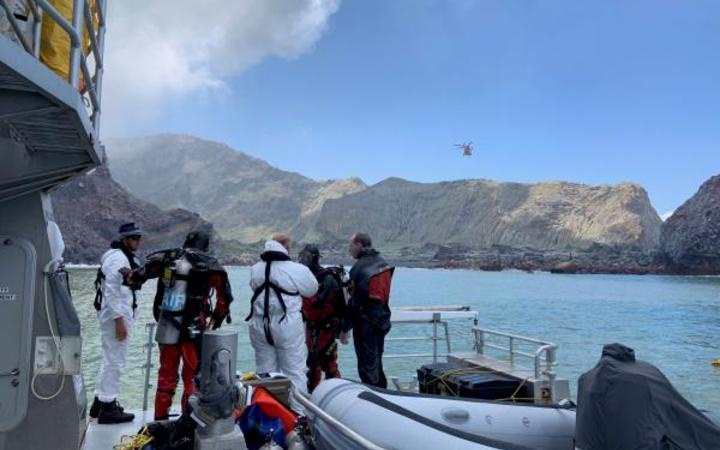 divers and others on a police boat off Whakaari