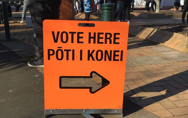 a pavement sign saying 'vote here'