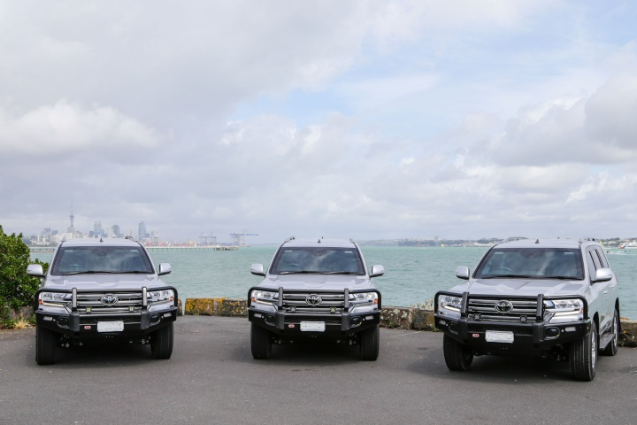 three Armoured Special Purpose Vehicles on the waterfront with a view over the habour to auckland city