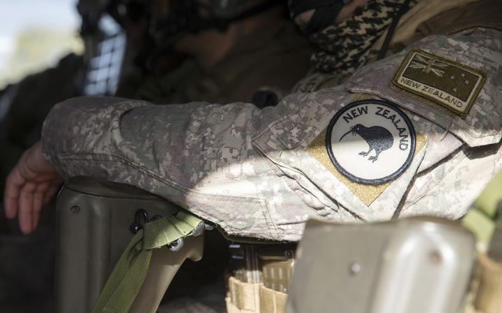 close up of a solider in a helicopter, showing the camouflage uniform arm with NZDF badges